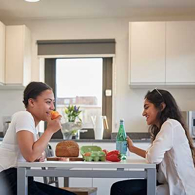 2 students talk over lunch in their shared flat