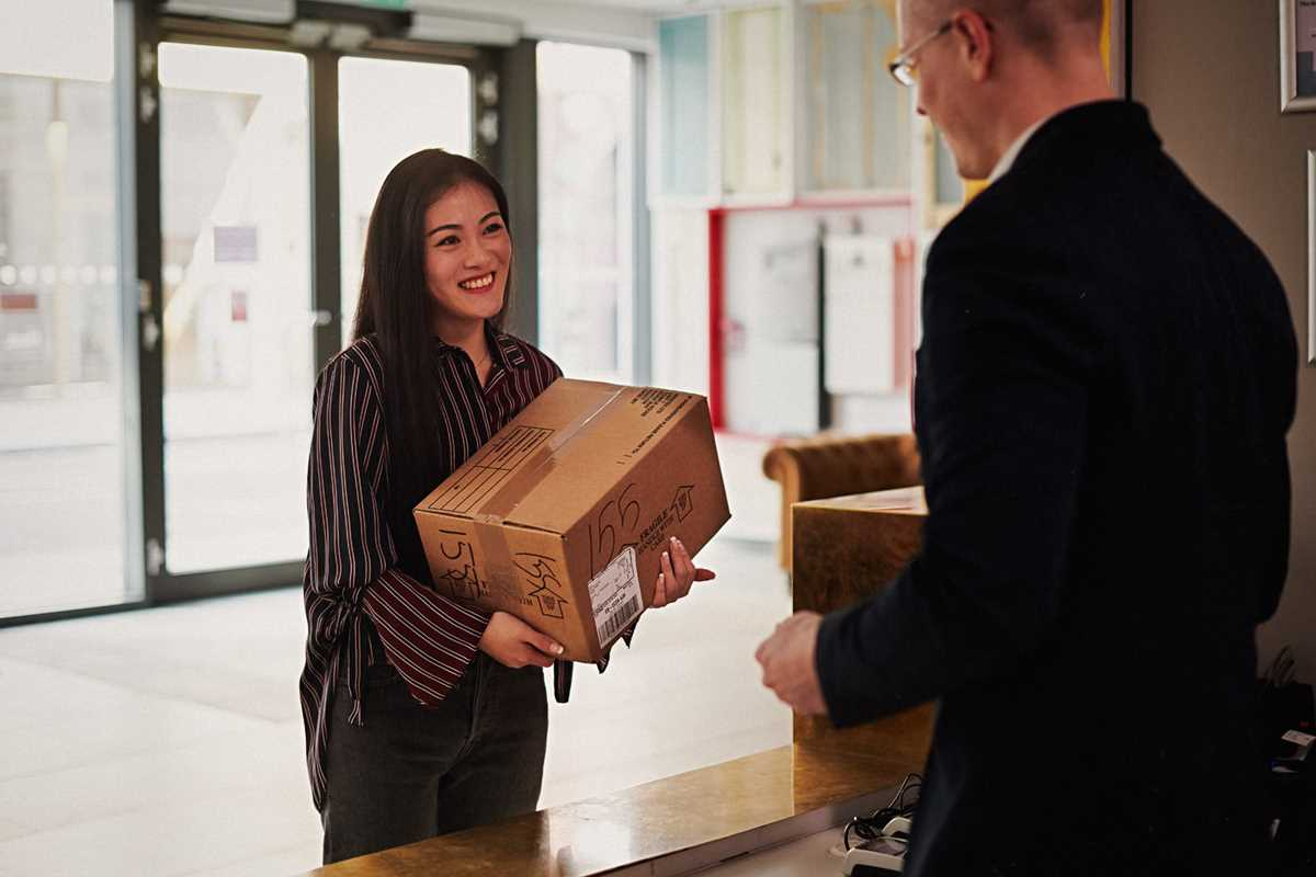 Student receiving package from Chapter Old Street reception staff